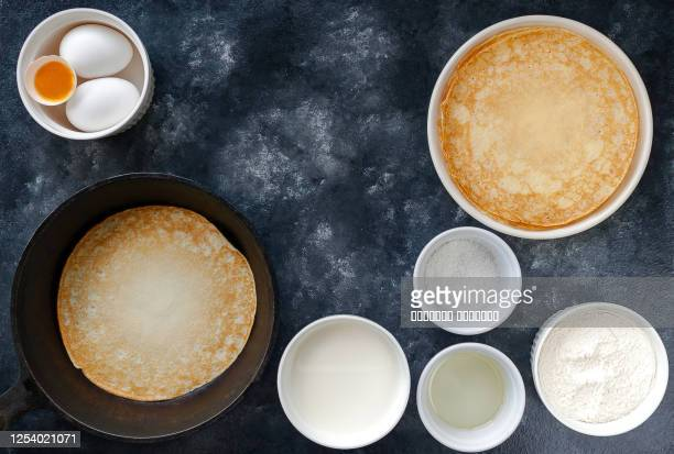 homemade crepes pancakes in cast iron pan and cooking ingredients over rustic black background - pancakes stock pictures, royalty-free photos & images