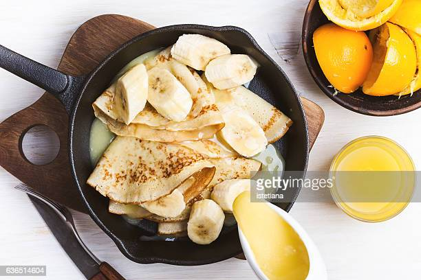 Homemade crepes with bananas and  white caramel sauce