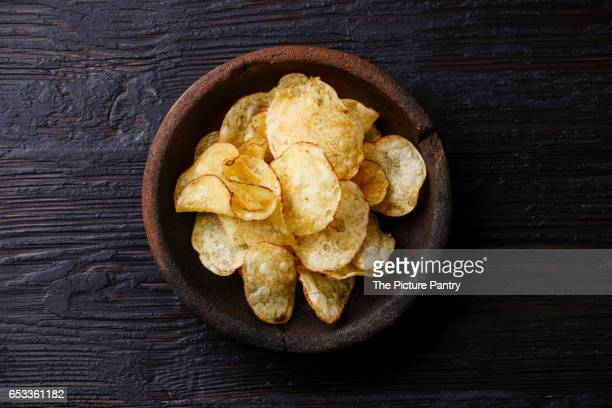 Homemade crunchy Potato chips on burned black wooden background