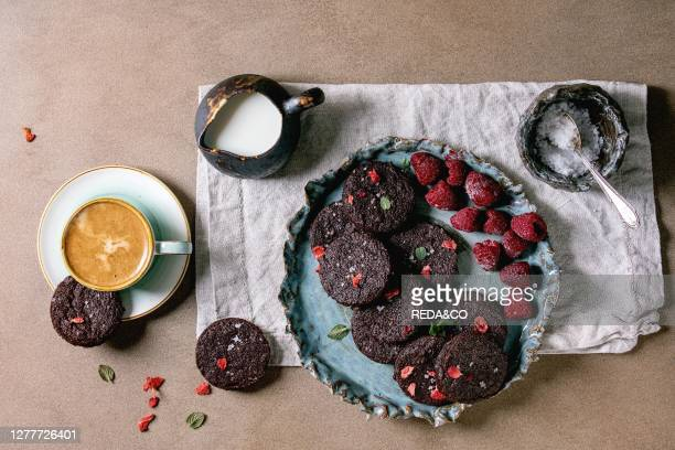 Homemade dark chocolate salted brownies cookies decorated by dry and fresh raspberries, served with salt flakes, berries, mint, milk and cup of...