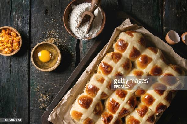Homemade Easter traditional hot cross buns on oven tray with baking paper and ingredients above over dark wooden background Top view space Rustic...