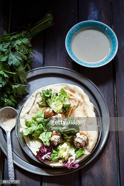 Homemade falafel with salad, tahini sauce on flat bread