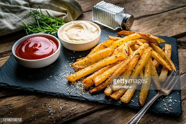 eigengemaakte frieten met ketchup en mayonaise op rustieke houten lijst - portie stockfoto's en -beelden
