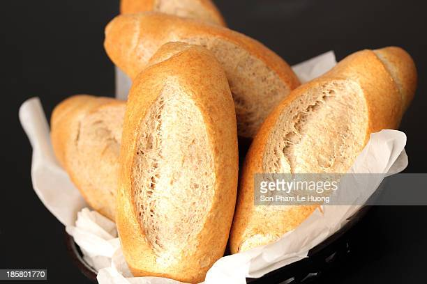 Homemade french style bread loaves in the basket on black background