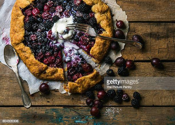 Homemade garden berry galetta or crostata sweet pie with melted vanilla ice-cream scoop