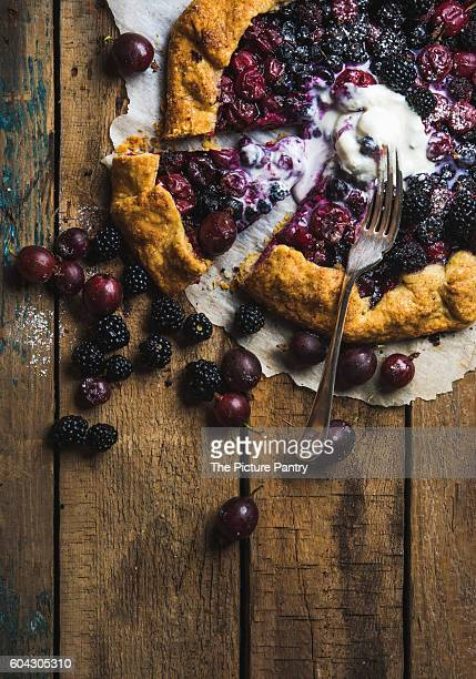Homemade garden berry galetta or crostata sweet pie with melted vanilla ice-cream scoop served with fresh berries on rustic wooden background