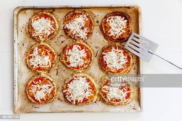 Homemade glutenfree mini pizzas with cauliflower and pumpkin on baking tray