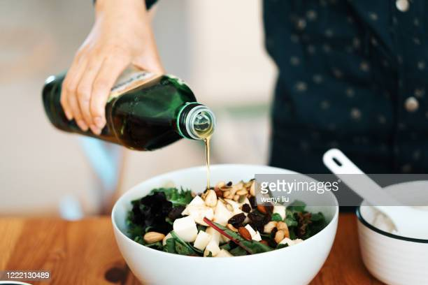 homemade gourmet food: fresh green salad with mozzarella, mixed nuts and dry fruits - olive oil stock pictures, royalty-free photos & images