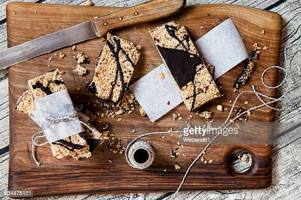 Homemade granola bars with amaranth and black chocolate on wooden board