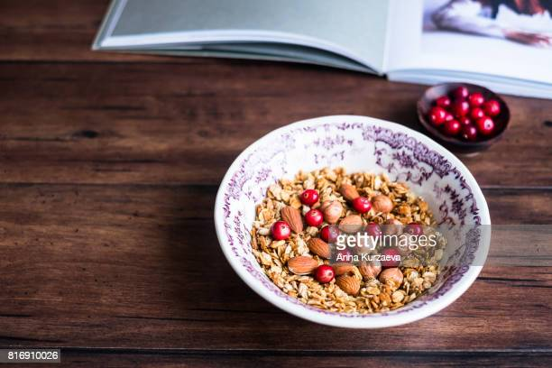 Homemade granola or muesli with oat flakes, almonds, hazelnuts and fresh cranberry in a bowl, selective focus