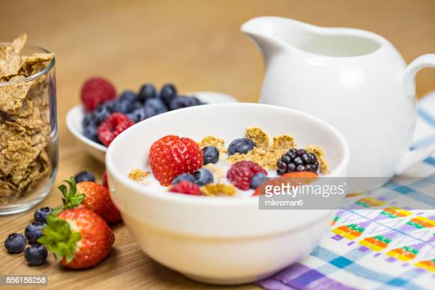 Homemade granola or muesli with oat flakes, corn flakes, dried fruits with fresh berries in a bowl, selective focus. Healthy Breakfast