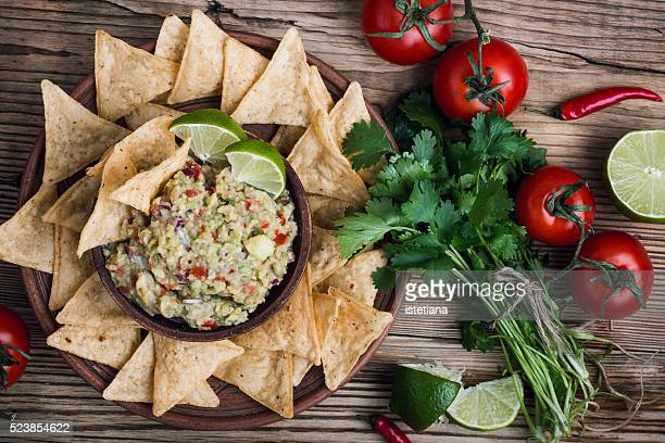 Homemade guacamole sauce and corn chips in ceramic bowl on wooden table viewed from above, Mexican food