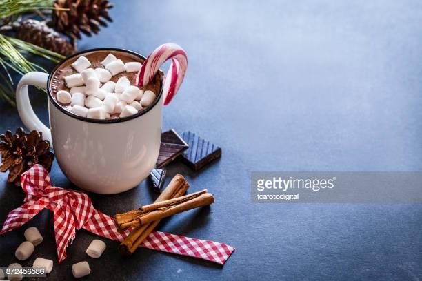 Casera taza de chocolate caliente con malvaviscos en la mesa de Navidad de madera rústico