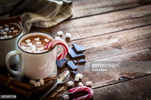 素朴な木製のクリスマス テーブルの上にマシュマロと自家製ホット チョコレート マグカップ