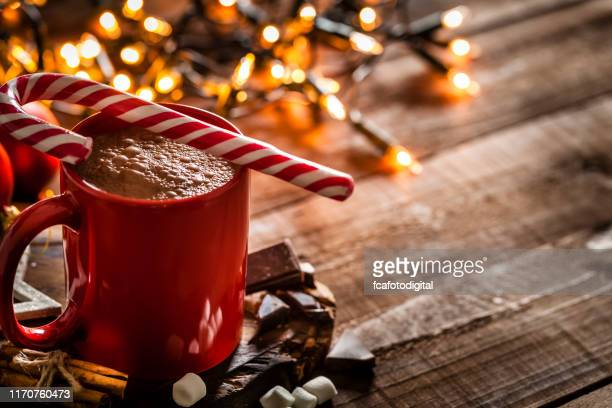 homemade hot chocolate mug with red and white candy cane on rustic wooden christmas table - candy cane stock pictures, royalty-free photos & images