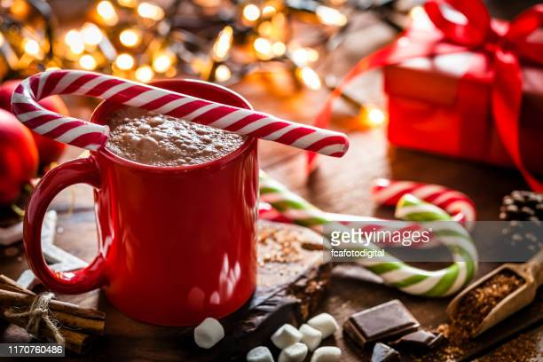 homemade hot chocolate mug with red and white candy cane on rustic wooden christmas table - hot chocolate stock pictures, royalty-free photos & images