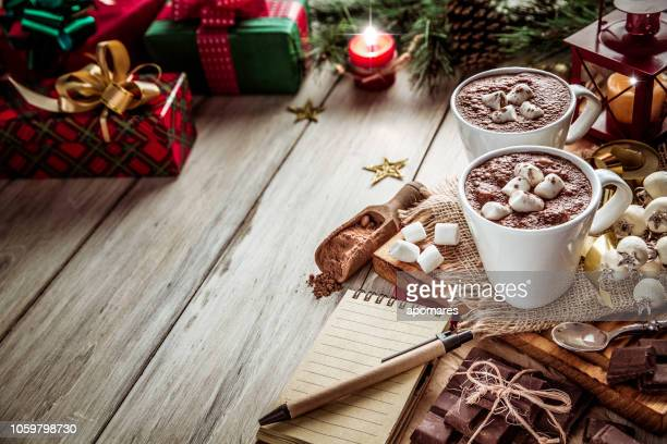 homemade hot chocolate mugs with marshmallows on rustic wooden table with candlelight and note pad. christmas themes. - list stock pictures, royalty-free photos & images