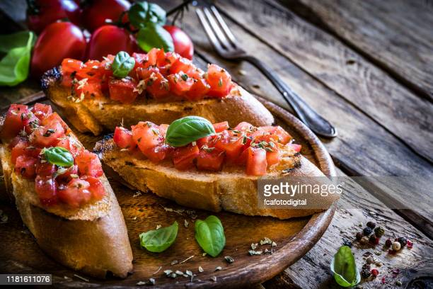 homemade italian bruschetta on rustic wooden table - antipasto stock pictures, royalty-free photos & images