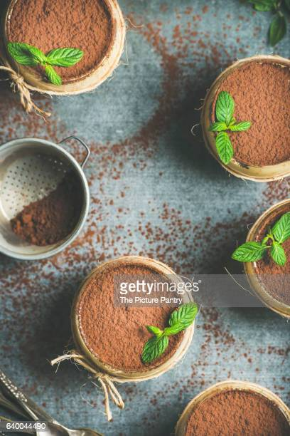 Homemade Italian dessert Tiramisu served in individual glasses with mint leaves and cocoa powder over grey concrete background