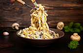 Homemade Italian fettuccine pasta with mushrooms and cream sauce (Fettuccine al Funghi Porcini). Traditional Italian cuisine. Served on a dark table with a rustic wooden background. Close-up