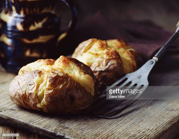Home-made jacket potatoes with cheddar cheese on rustic wooden board