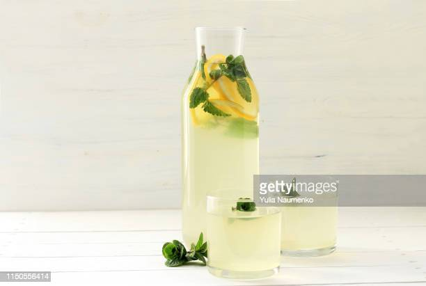 homemade lemonade in bottle, lemons on wooden background. made from lemon and mint. - ジュース ストックフォトと画像
