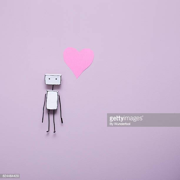 Homemade little robot next to a pink heart seen from above on a purple background