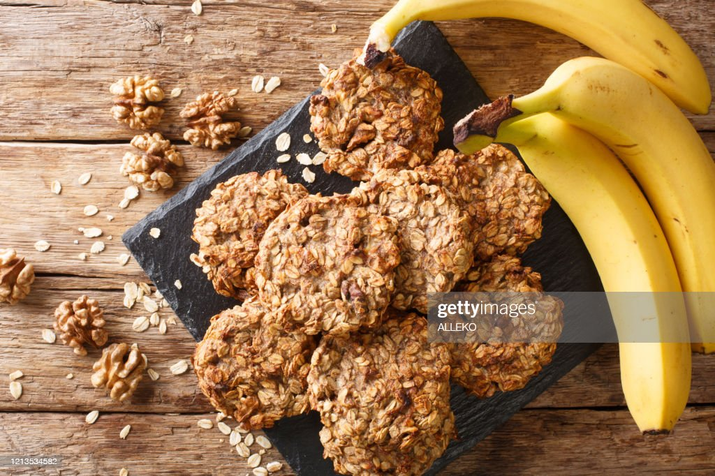 Homemade low-calorie banana cookies with oatmeal and walnuts close-up on a slate board. Horizontal top view : Stock Photo