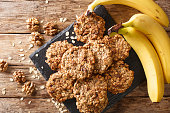 Homemade low-calorie banana cookies with oatmeal and walnuts close-up on a slate board. Horizontal top view