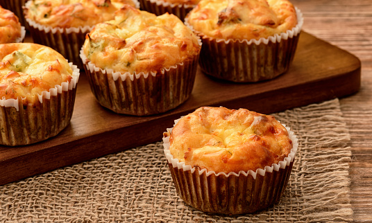 Homemade muffins with chicken and cheese on brown wooden board. 525364108
