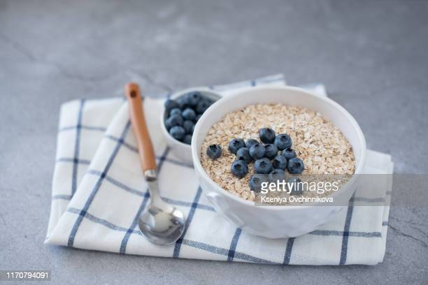 homemade oatmeal with blueberries and strawberries in bowl on gray concrete background. healthy breakfast. - wholegrain stock pictures, royalty-free photos & images