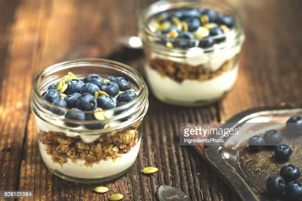 Maison organique yogourt avec granola et bleuets sur une table en bois rustique.