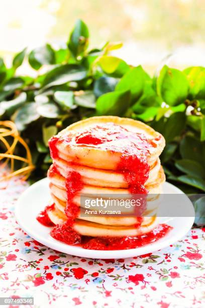 Homemade pancakes with berry jam stacked on a plate, selective focus
