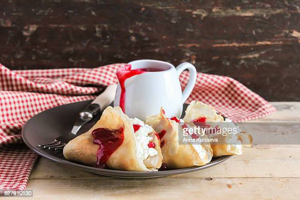 Homemade pancakes with cottage cheese and cranberry sauce on a plate