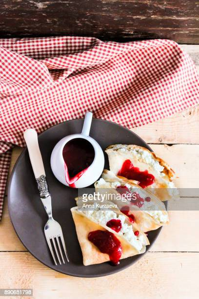 Homemade pancakes with cottage cheese and cranberry sauce on a plate, top view