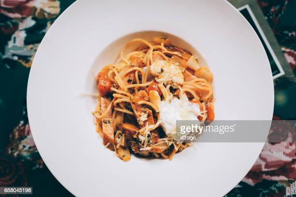 Homemade pasta with chicken and mushroom on bolognese sauce freshly served in plate