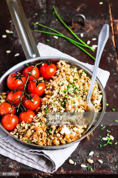 Homemade pie or crumble with white fish fillet, sunflower and flax seeds and roasted cherry tomatoes in a pan on a wooden table, selective focus