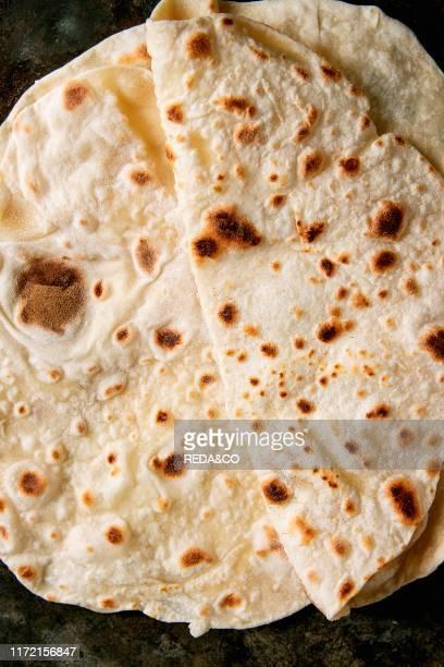 Homemade pita or chapati flatbread flapjack over dark metal background Flat lay close up