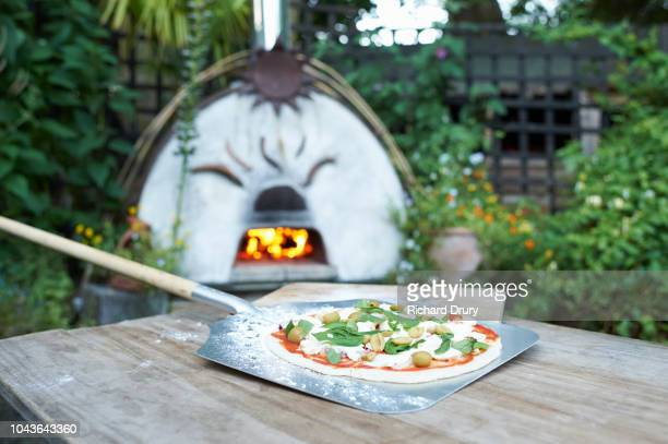 homemade pizza on a pizza peel - pizza oven stock photos and pictures