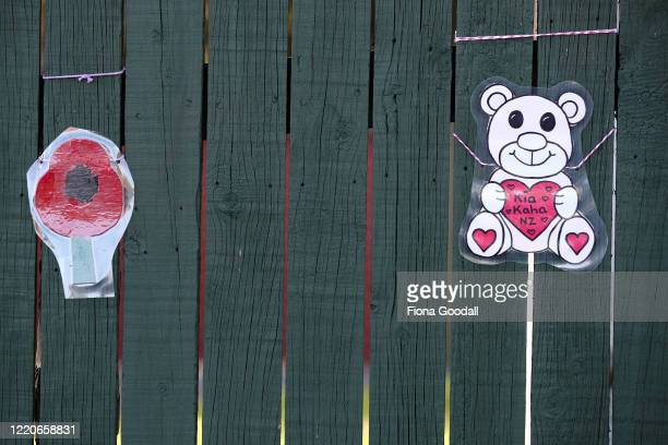 Homemade poppies hang on a fence in Titirangi to mark Anzac Day on April 24 2020 in Auckland New Zealand New Zealanders are preparing to commemorate...