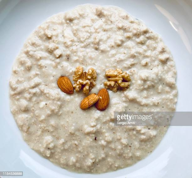 homemade porridge with almond and walnuts - sergio amiti stock pictures, royalty-free photos & images