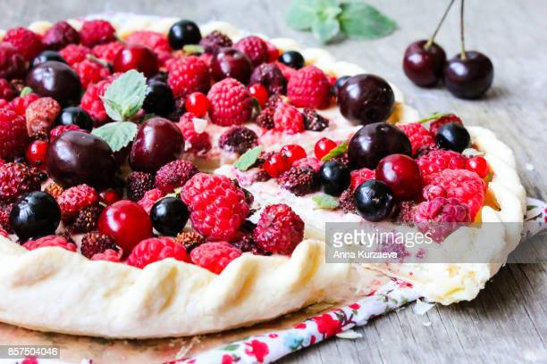 homemade puff pastry sweet pie with fresh cherry, raspberry, black currant and strawberry with cream cheese decorated with fresh mint on a wooden table, selective focus - mascarpone cheese stock pictures, royalty-free photos & images