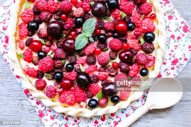 Homemade puff pastry sweet pie with fresh cherry, raspberry, black currant and strawberry with cream cheese decorated with fresh mint on a wooden table, top view