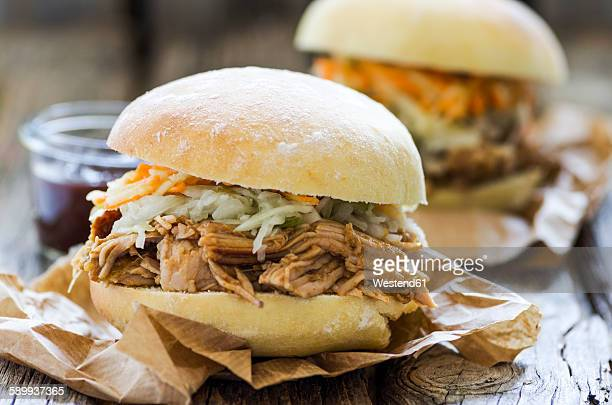 Homemade pulled pork with carrot and cabbage salad on hamburger bun