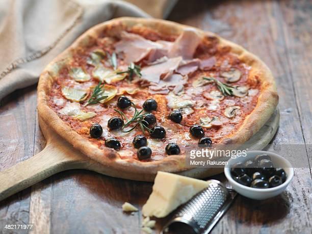Homemade quattro stagioni pizza with ham, artichokes, olives, mushrooms and mozzarella cheese