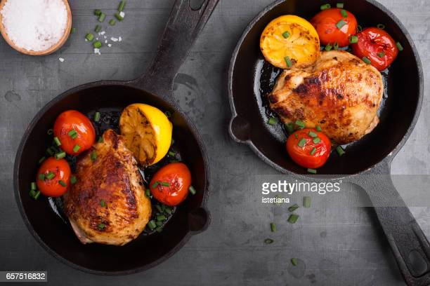 Homemade roasted chicken thighs with lemon and tomatoes in cast iron pan