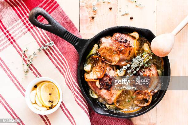 Homemade roasted chicken with lemon and garlic in a pan on a wooden table, top view
