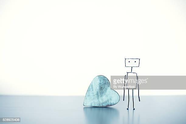 Homemade robot next to a wooden heart