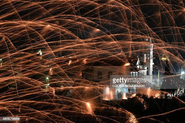 Homemade rockets streak through the sky during a traditional Easter celebration in the village of Vrontados on the Greek island of Chios late on...