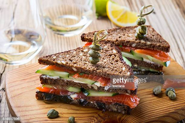 homemade salmon club sandwich on rye bread with cucumber and sauteed spinach and secure with cocktail sticks - club sandwich stock pictures, royalty-free photos & images
